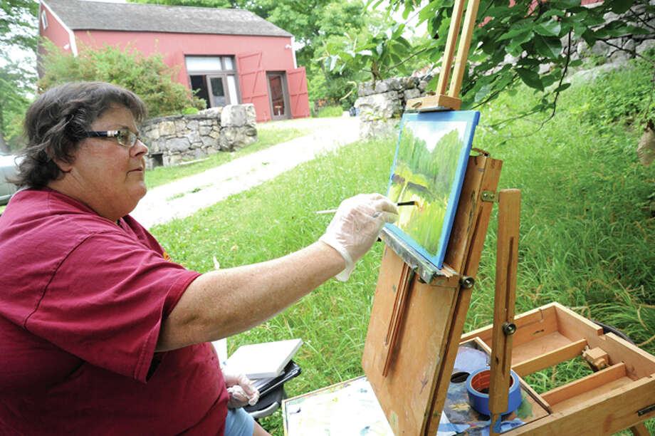 Julie Barnett works on her oil painting Sunday at Weir Farm in Wilton as part of a workshop led by artist Dimitri Wright.