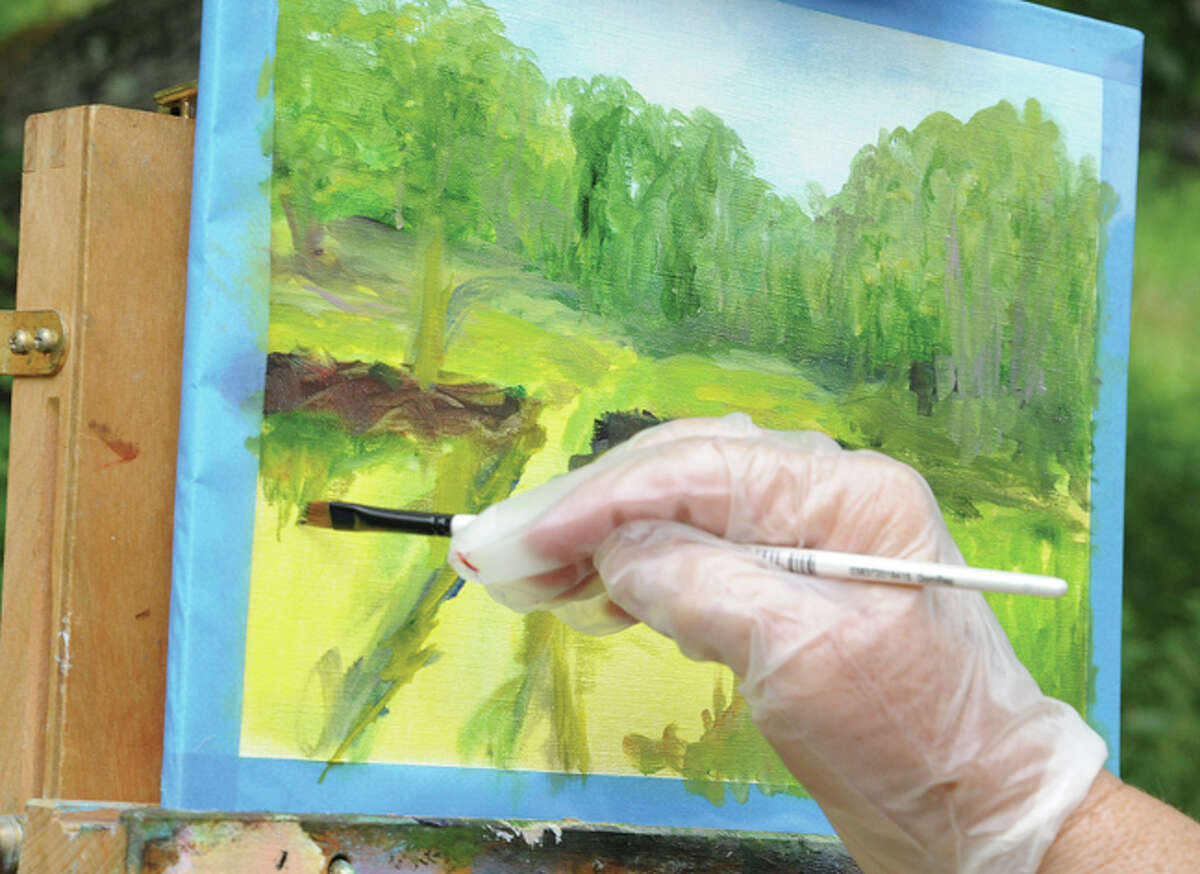 An artist works on a oil painting Sunday at Weir Farm in Wilton as part of a workshop led by artist Dimitri Wright.