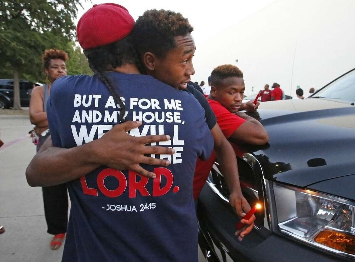 People comfort on another at the candlelight vigil for Christian Taylor, held in the parking lot of Koinonia Christian Church in Arlington, Texas, Saturday, Aug. 8, 2015. The FBI has been asked to help investigate the death of Taylor, a Texas college football player, who was fatally shot by an officer during a burglary call at a car dealership, a suburban Dallas police chief said Saturday. (Louis DeLuca/The Dallas Morning News via AP) MANDATORY CREDIT; MAGS OUT; TV OUT; INTERNET USE BY AP MEMBERS ONLY; NO SALES