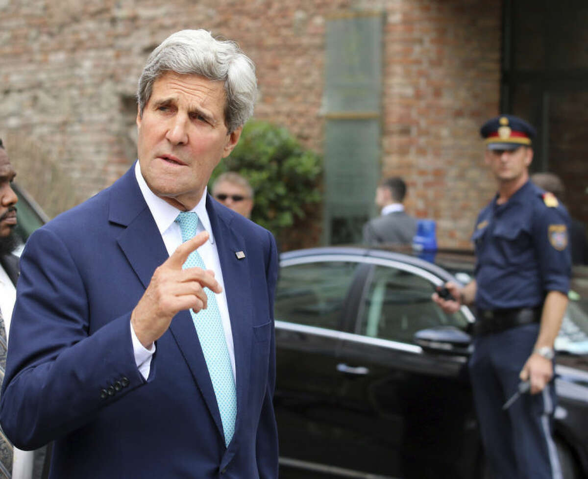 U.S. Secretary of State John Kerry gestures as he arrives in front of a hotel where closed-door nuclear talks on Iran take place in Vienna, Austria, Sunday, July 13, 2014. Kerry and fellow foreign ministers are adding their diplomatic muscle to nuclear talks with Iran, with a target date only a week away for a pact meant to curb programs Tehran could turn to making atomic arms. (AP Photo/Ronald Zak)