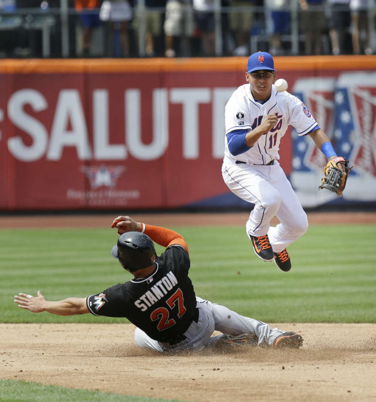 New York Mets shortstop Ruben Tejada, right, turns a double play on Miami Marlins' Giancarlo Stanton during the sixth inning of the baseball game at Citi Field, Sunday, July 13, 2014 in New York. (AP Photo/Seth Wenig)