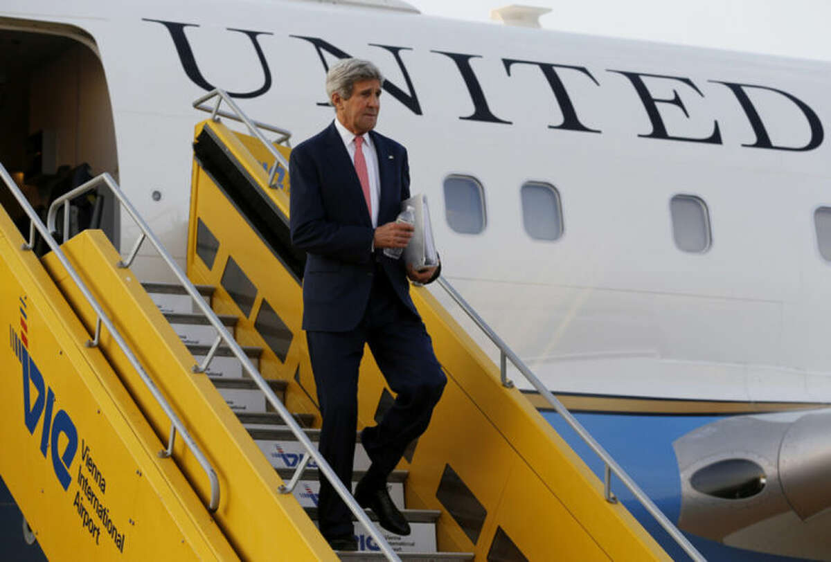 U.S. Secretary of State John Kerry steps out his plane upon arrival at Vienna International Airport for talks with foreign ministers from the six nations negotiating with Tehran on its nuclear program in Vienna, Sunday, July 13, 2014. (AP Photo/Jim Bourg, Pool)