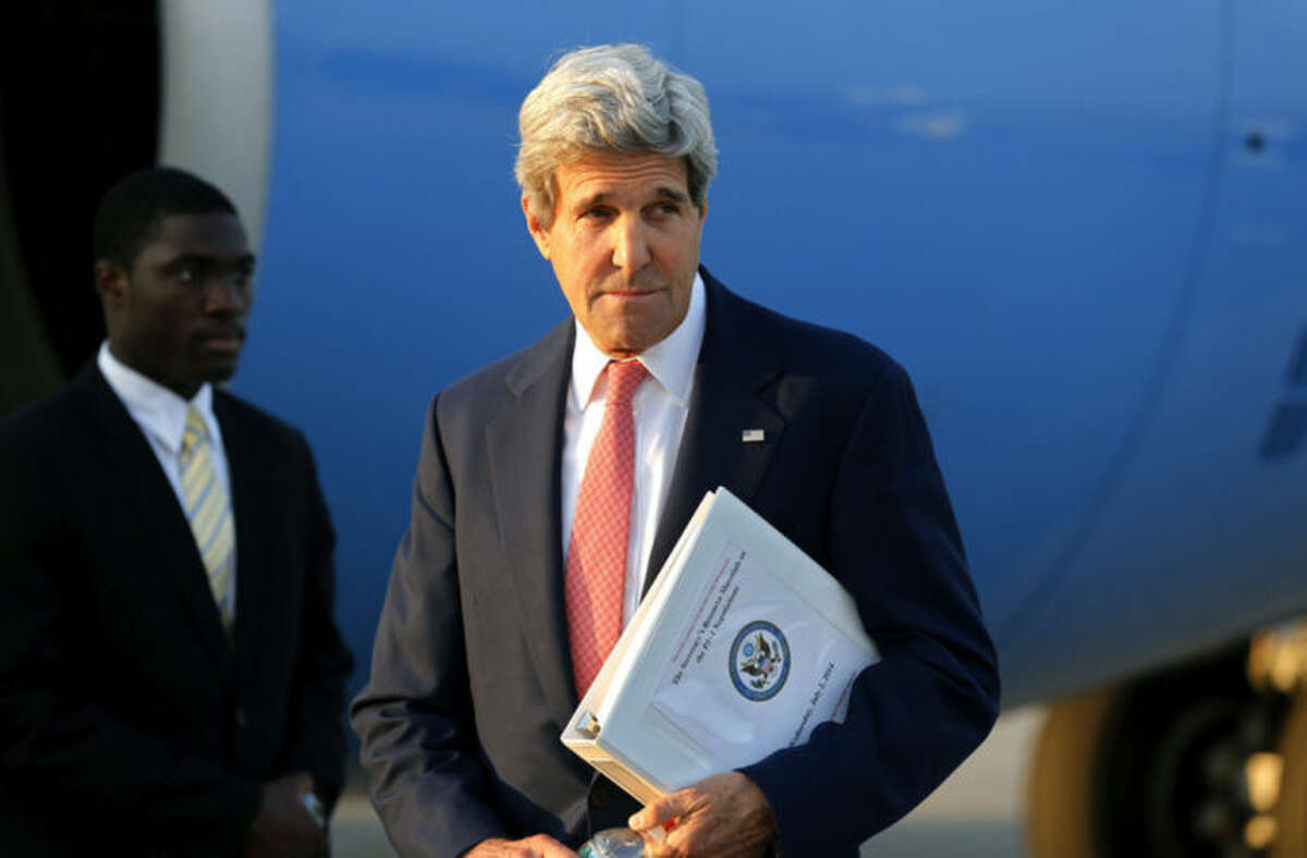 U.S. Secretary of State John Kerry leaves his plane at Vienna International Airport as he arrives for talks with foreign ministers from the six powers negotiating with Tehran on its nuclear program in Vienna, Sunday, July 13, 2014. (AP Photo/Jim Bourg, Pool)