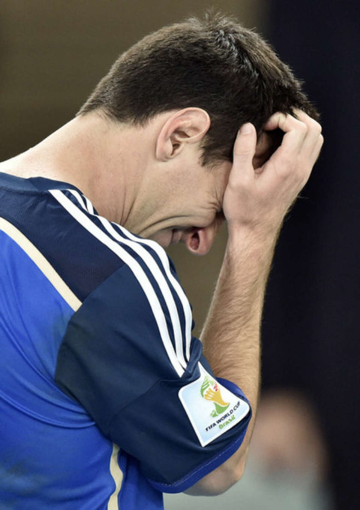 Argentina's Lionel Messi goes to get his runner-up medal after the World Cup final soccer match between Germany and Argentina at the Maracana Stadium in Rio de Janeiro, Brazil, Sunday, July 13, 2014. Germany won the match 1-0 (AP Photo/Martin Meissner)