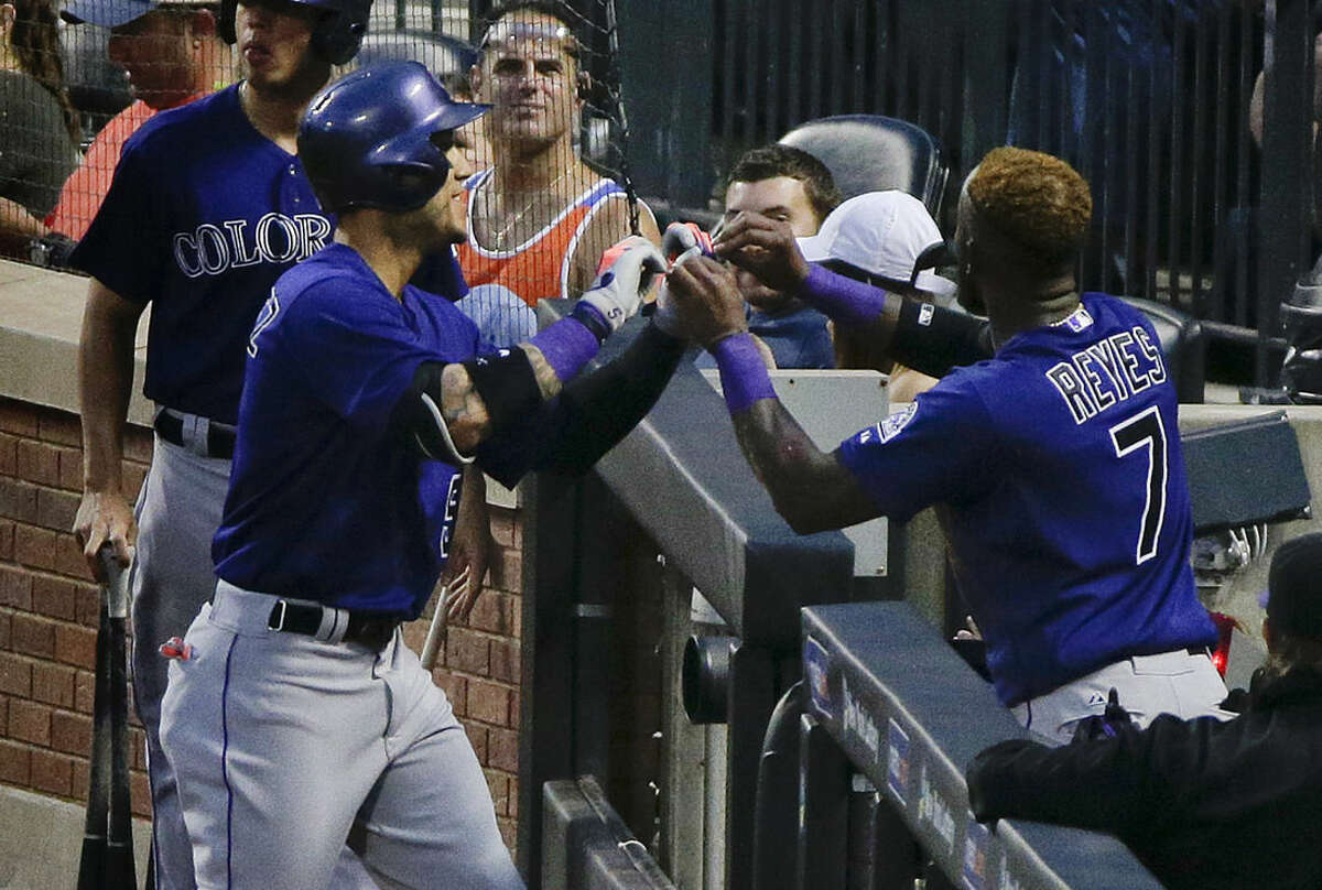Colorado Rockies' Carlos Gonzalez, left, is greeted in the dugout by Jose Reyes after hitting a two-run home run against the New York Mets during the fourth inning of a baseball game, Monday, Aug. 10, 2015, in New York. (AP Photo/Julie Jacobson)
