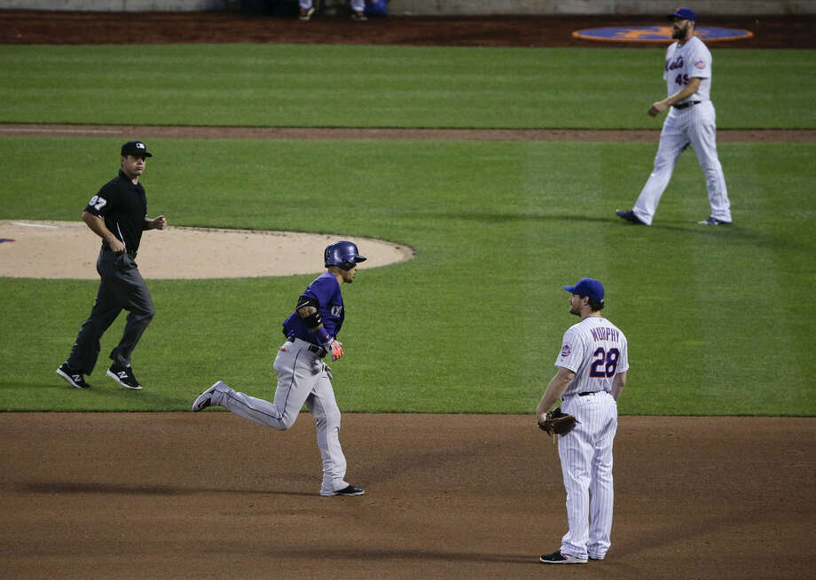 Colorado Rockies' Carlos Gonzalez, second from left, rounds the bases after hitting a two-run home run during the fourth inning of a baseball game, Monday, Aug. 10, 2015, in New York, New York Mets second baseman Daniel Murphy (28), pitcher Jonathon Niese and umpire Ben May (97) look on. (AP Photo/Julie Jacobson)