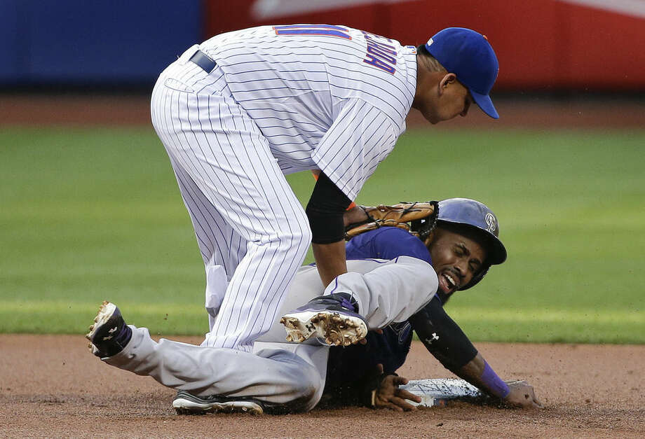 Colorado Rockies' Jose Reyes, right, reacts as he is tagged out by New York Mets shortstop Ruben Tejada (11) while trying to steal second base during the first inning of a baseball game, Monday, Aug. 10, 2015, in New York. (AP Photo/Julie Jacobson)