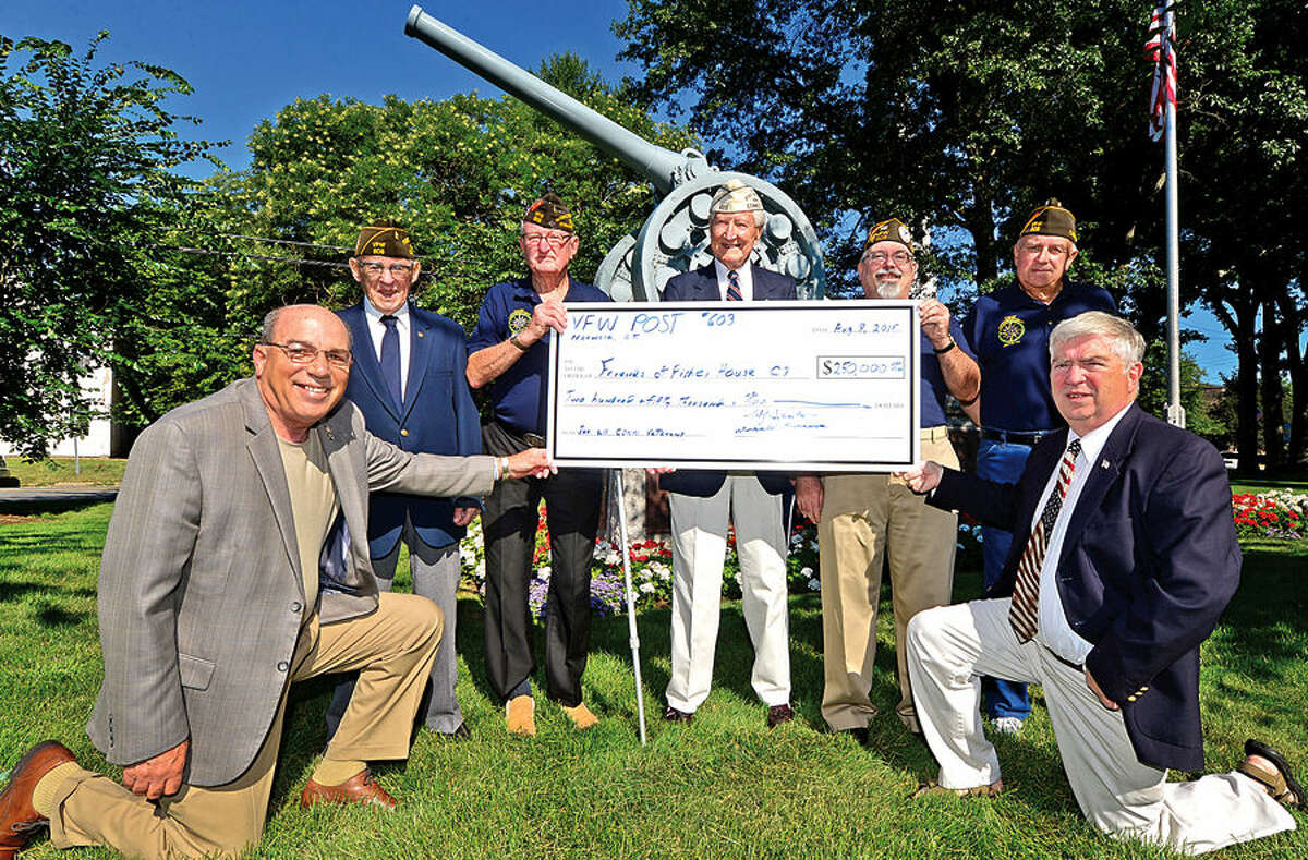 Hour photo / Erik Trautmann Tom Flowers and Kevin Creed of Fisher House CT, (kneeling) receive a check for $250,000 from VFW Post 603 veteran's Hugh Sebastian, Don Burrows, Edward Zamm, John Grindstaff and John Barry, during a brief ceremony Saturday on Norwalk Green.