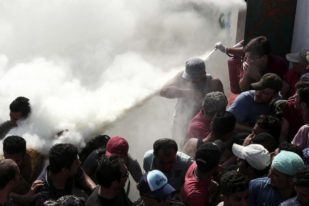 Policemen try to disperse hundreds of migrants by spraying them with fire extinguishers, during a registration procedure which was taking place at the stadium of Kos town, on the southeastern island of Kos, Greece, Tuesday, Aug. 11, 2015. Fights broke out among migrants on the Greek island of Kos Tuesday, where overwhelmed authorities are struggling to contain increasing numbers of people arriving clandestinely on rubber dinghies from the nearby Turkish shore. (AP Photo/Yorgos Karahalis)