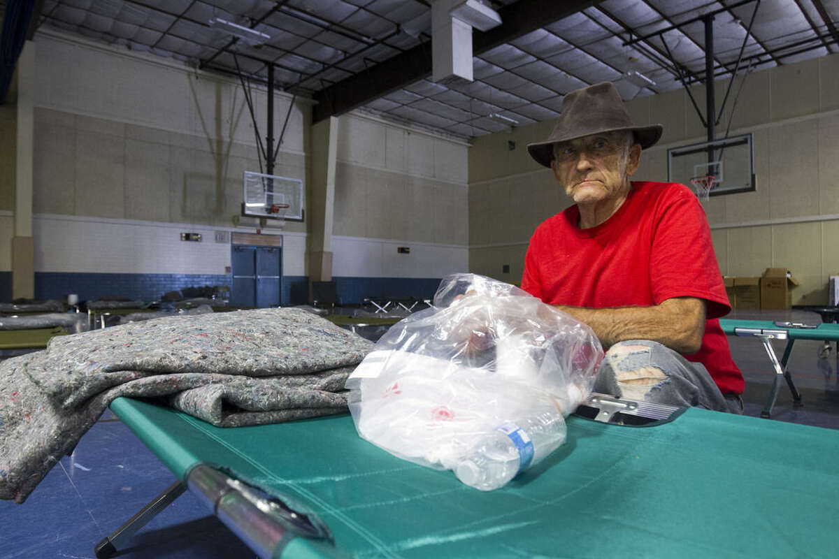 In this Monday, Aug. 10, 2015, photo, Gerald Jesionka, 78, sits in a Red Cross shelter set up in an elementary school gym in Mohave Valley, Ariz. Jesionka said he escaped the Willow Fire with only his mother's ashes and his pit bull Baby.