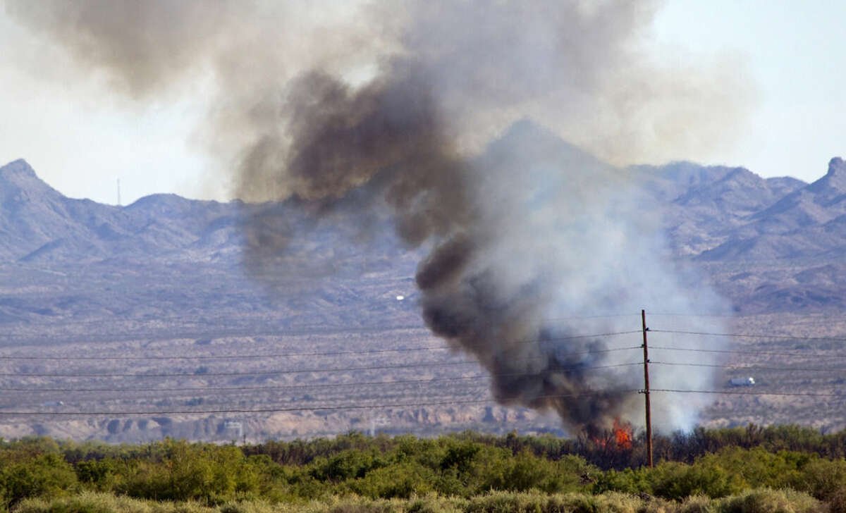 In this Monday, Aug. 10, 2015, photo, a section of brush flares up near power lines at the Willow Fire in Mohave Valley, Ariz. Authorities said 300 firefighters are battling the fire amid strong winds and low humidity. (Steve Marcus/Las Vegas Sun via AP)