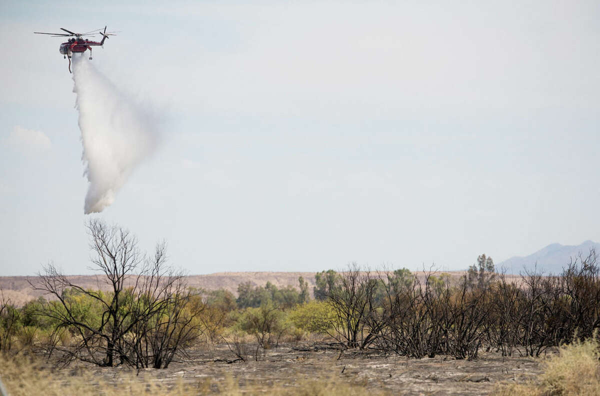 A helicopter helps put out part of a wildfire near Needles, Calif., Monday, Aug. 10, 2015. Wildfire crews battling a rapidly growing fire on the Arizona-California border near the Colorado River have called in help from California, Oregon and Washington states. (Michael Schennum/The Arizona Republic via AP)
