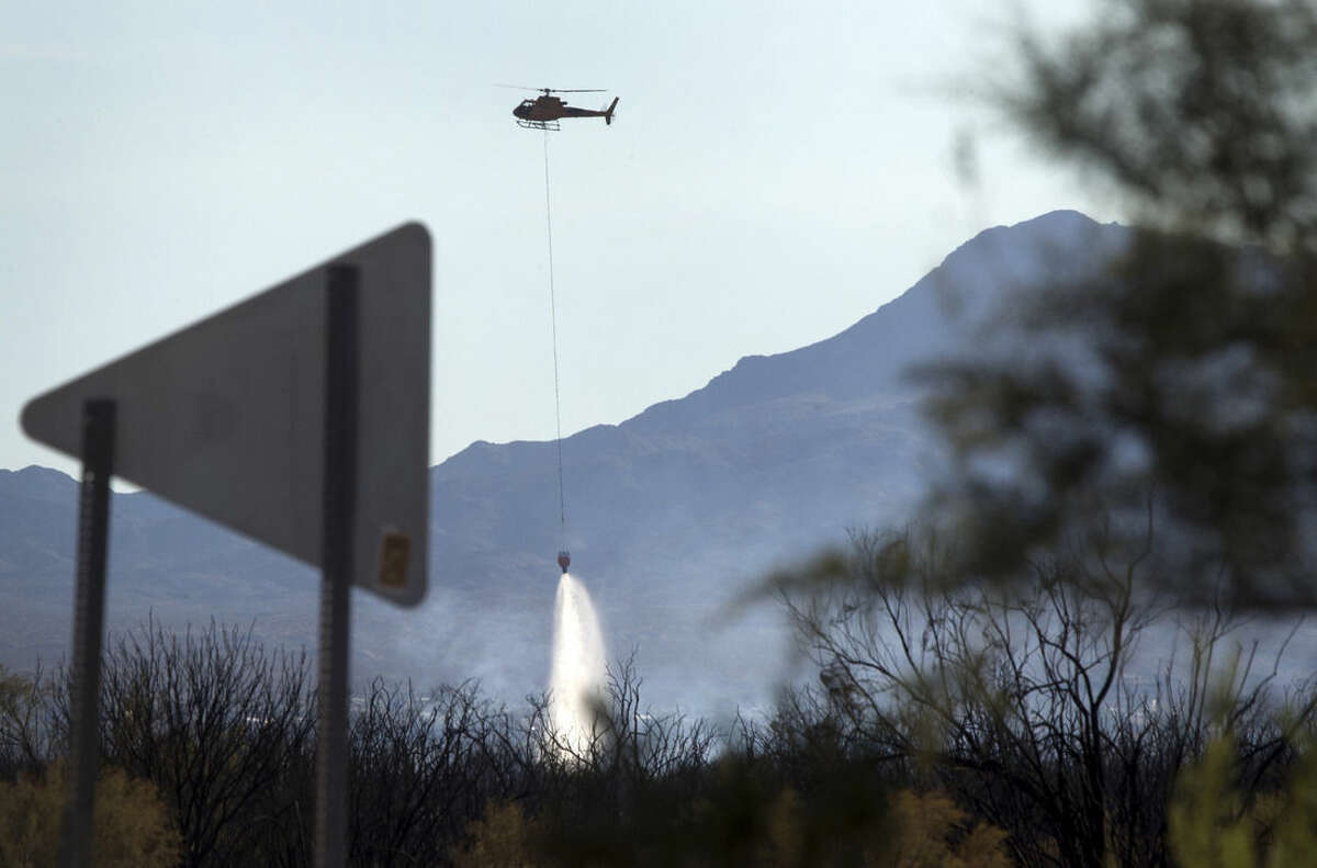 In this Monday, Aug. 10, 2015, photo, a helicopter drops water on the Willow Fire in Mohave Valley, Ariz. Authorities said 300 firefighters are battling the fire amid strong winds and low humidity. (Steve Marcus/Las Vegas Sun via AP)