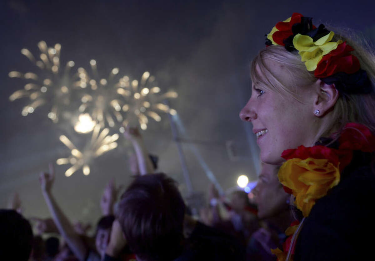 Fireworks illuminate the sky as German fans celebrate their team after Germany won against Argentina by 1-0 at the soccer World Cup final in Rio de Janeiro, Brazil, at a public viewing area called 'Fan Mile' in Berlin, Sunday, July 13, 2014. (AP Photo/dpa,.Britta Pedersen)