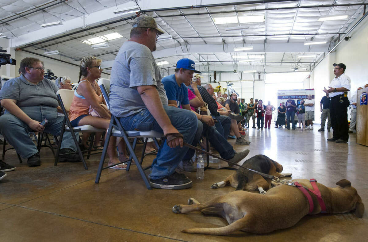 In this Monday, Aug. 10, 2015, photo, displaced residents listen to Mohave Valley Fire Marshal Don Gibson, right, during a public meeting on the Willow Fire at Fire Station 81, in Mohave Valley, Ariz. Authorities said 300 firefighters are battling the fire amid strong winds and low humidity. (Steve Marcus/Las Vegas Sun via AP)