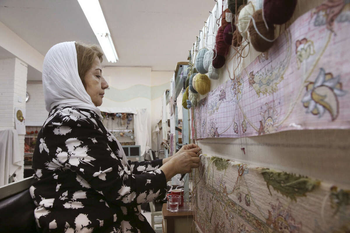 In this Tuesday, Aug. 4, 2015 photo, an Iranian woman weaves a carpet at a workshop by the Cultural and Artistic Carpet Foundation of Rassam Arabzadeh in Tehran, Iran. Iran's famed carpet weavers are busy at work following the country's historic nuclear deal with world powers, anticipating a boost in exports as sanctions are set to be lifted in the months ahead. (AP Photo/Vahid Salemi)