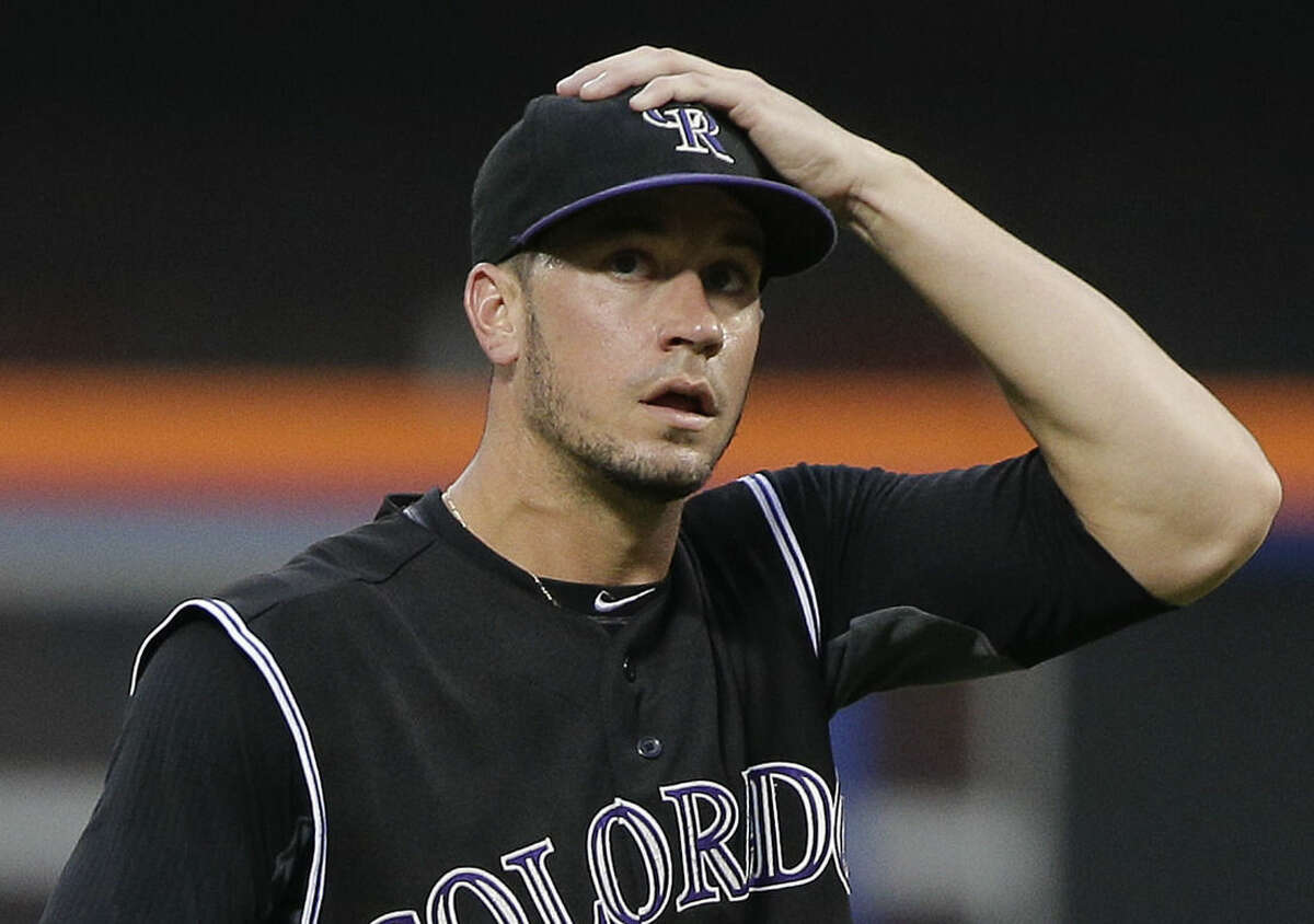 Colorado Rockies pitcher Chris Rusin adjusts his cap between batters during the first inning of a baseball game against the New York Mets, Tuesday, Aug. 11, 2015, in New York. (AP Photo/Julie Jacobson)