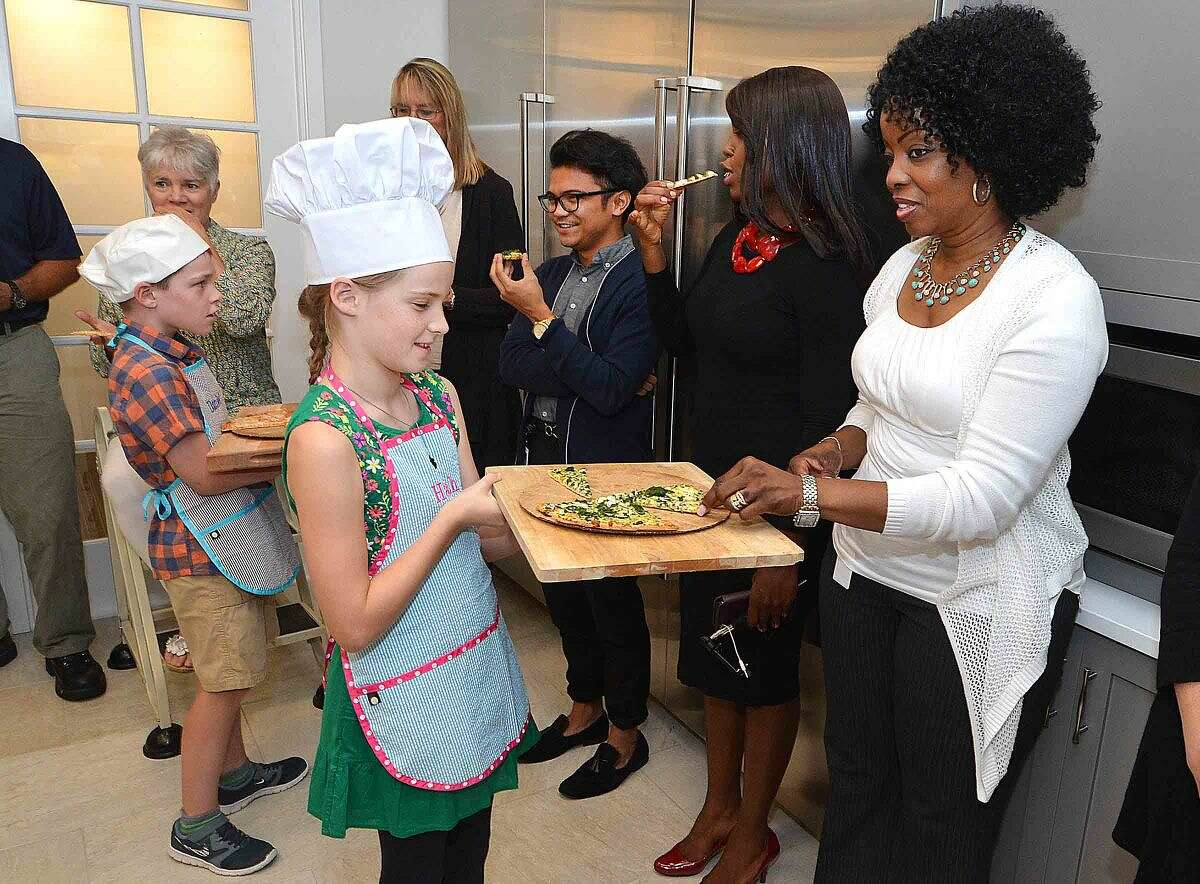 Hour Photo/Alex von Kleydorff 10yr old Hannah Betts and brother Daniel pass around some of the pizzas to employees at Newman's Own in Westport, as the Connecticut winner of 'The Healthy Lunchtime Challenge' she was honored with other winners at The White House Kids