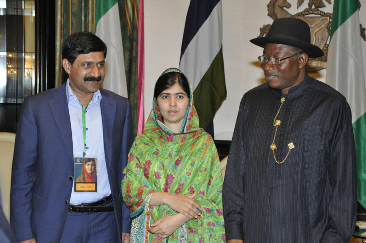 Pakistani activist Malala Yousafzai, centre, poses for a photo with her father Ziauddin left, and Nigerian President, Goodluck Jonathan, at the Presidential villa, in Abuja, Nigeria, Monday, July 14, 2014. Malala Yousafzai won a promise from Nigeria?'s leader to meet with the parents of some of the 219 schoolgirls held by Islamic extremists for three months. Malala celebrated her 17th birthday on Monday in Nigeria with promises to work for the release of the girls from the Boko Haram movement. (AP Photo)