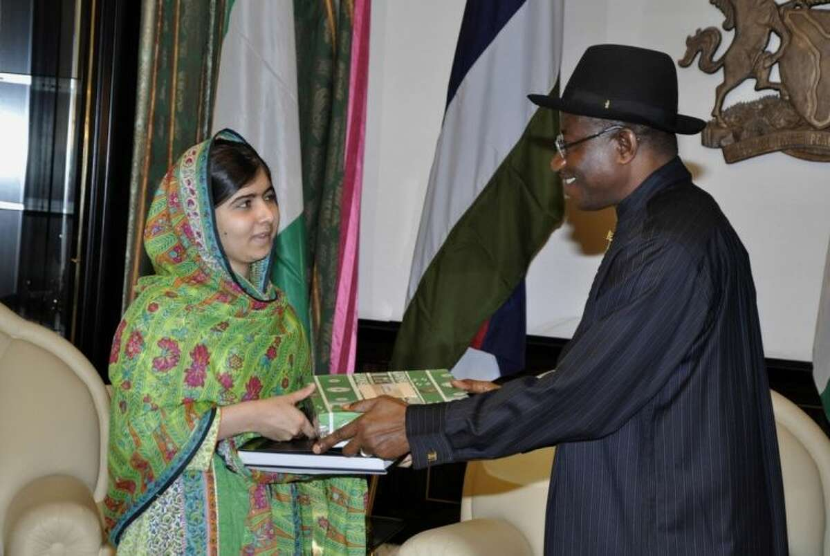 Pakistani activist Malala Yousafzai, left, receives a gift from Nigerian President, Goodluck Jonathan, right, at the Presidential villa, in Abuja, Nigeria, Monday, July 14, 2014. Yousafzai on Monday won a promise from Nigeria?'s leader to meet with the parents of some of the 219 schoolgirls held by Islamic extremists for three months. Malala celebrated her 17th birthday on Monday in Nigeria with promises to work for the release of the girls from the Boko Haram movement. (AP Photo)
