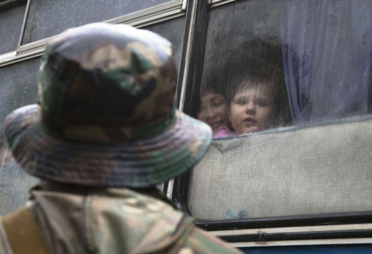 A Donetsk People's Republic fighter near a bus with his family departing as refugees to Russia in the city of Donetsk, eastern Ukraine Monday, July 14, 2014. Five busloads of Internally Displaced People from the towns of Slavyansk, Karlovka, Maryinka and Donetsk left here Monday morning for the Rostov region in Russia to ask for refugee status there. (AP Photo/Dmitry Lovetsky)