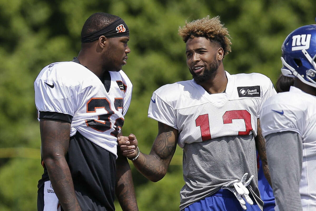 Cincinnati Bengals halfback Jeremy Hill, left, and New York Giants wide receiver Odell Beckham Jr. speak on the sidelines during a joint NFL football training camp, Wednesday, Aug. 12, 2015, in Cincinnati. (AP Photo/John Minchillo)