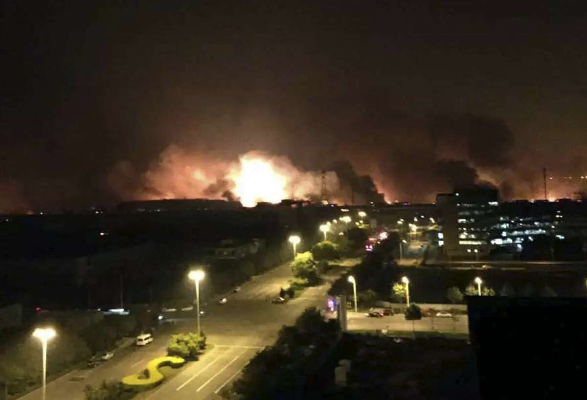 In this photo released by Xinhua News Agency smoke and fire erupt into the night sky after an explosion in the Binhai New Area in north China's Tianjin Municipality on Thursday Aug. 13, 2015. Chinese state media reported huge explosions at the Tianjin port late Wednesday with large numbers of people reported injured. (Yue Yuewei/Xinhua via AP) CHINA OUT - NO SALES