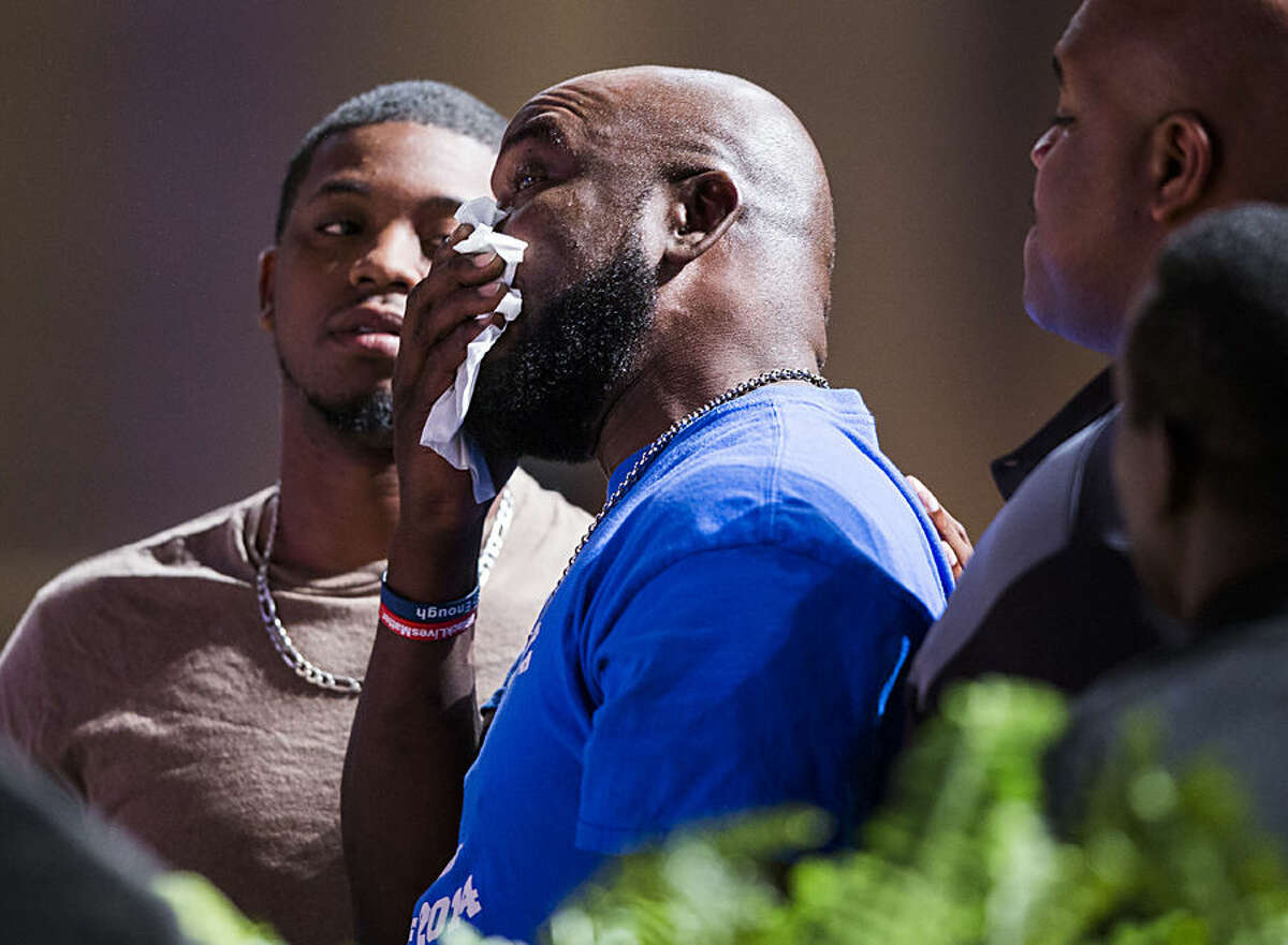 Adrian Taylor, middle, father of Christian Taylor, wipes away tears while standing between his sons Joshua, left, and Adrian Taylor, Jr. during a Unity, Peace and Prayer rally, Wednesday, Aug. 12, 2015, at Cornerstone Church in Arlington. Christian Taylor was fatally shot by a police officer during a suspected burglary at a car dealership on Friday, Aug. 7. (Ashley Landis/The Dallas Morning News via AP) MANDATORY CREDIT; MAGS OUT; TV OUT; INTERNET USE BY AP MEMBERS ONLY; NO SALES