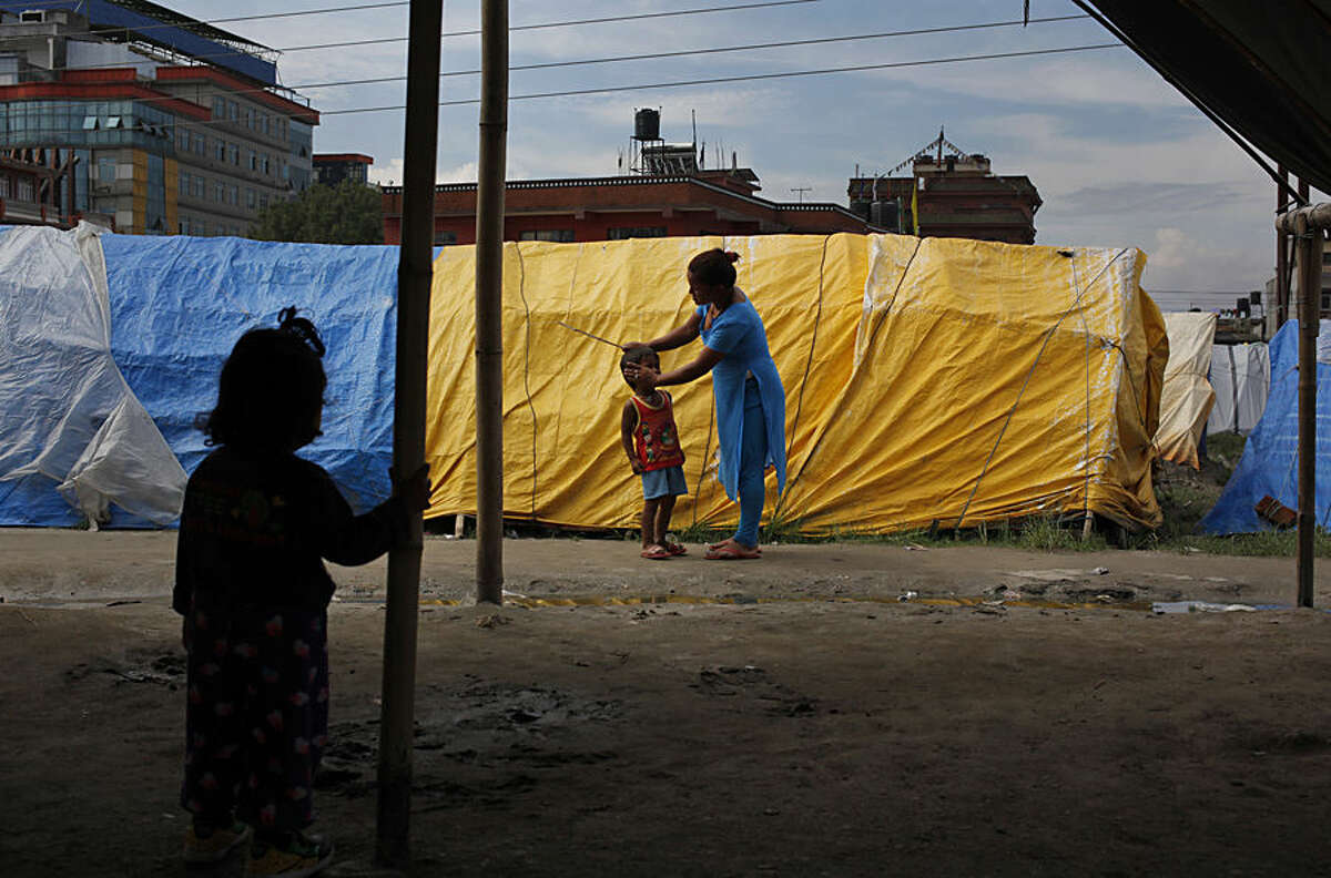 A Nepalese woman wipes her son's tears after yelling at him for playing in dirt at a camp for the earthquake affected in Chuchepati, Kathmandu, Nepal, Thursday, Aug 13, 2015. More than seven thousand earthquake-affected people are living in 970 tents in this camp that has only 35 toilets. The earthquake in April killed some 8,900 people and destroyed hundreds of thousands of houses. (AP Photo/Niranjan Shrestha)