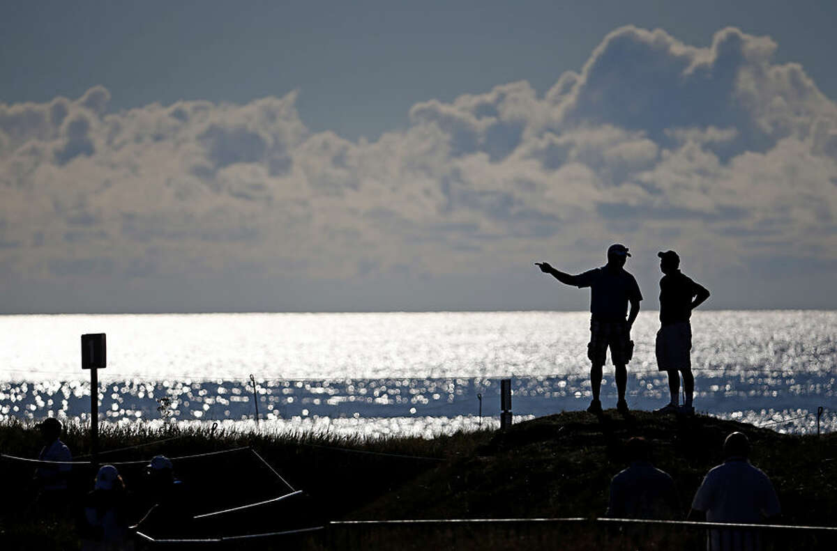 Fans look over the second hole during a practice round for the PGA Championship golf tournament Wednesday, Aug. 12, 2015, at Whistling Straits in Haven, Wis. (AP Photo/Julio Cortez)