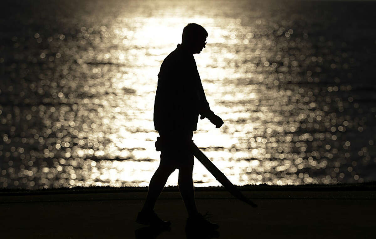 A worker blows off a green as the sun rises before a practice round for the PGA Championship golf tournament Wednesday, Aug. 12, 2015, at Whistling Straits in Haven, Wis. (AP Photo/Brynn Anderson)