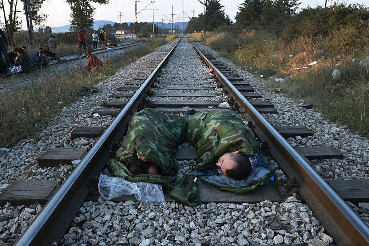 Syrian refugees sleep on railway lines near the train station of Idomeni, northern Greece, on Wednesday, Aug. 12, 2015. Greece is Europe's main entry point for people arriving by sea, as the alternative route from north Africa to Italy has become increasingly dangerous due to fighting in Libya. From Greece, the migrants move north through the Balkans, hoping to gain asylum, preferably in Germany, the Netherlands or Scandinavia. (AP Photo/Giannis Papanikos)