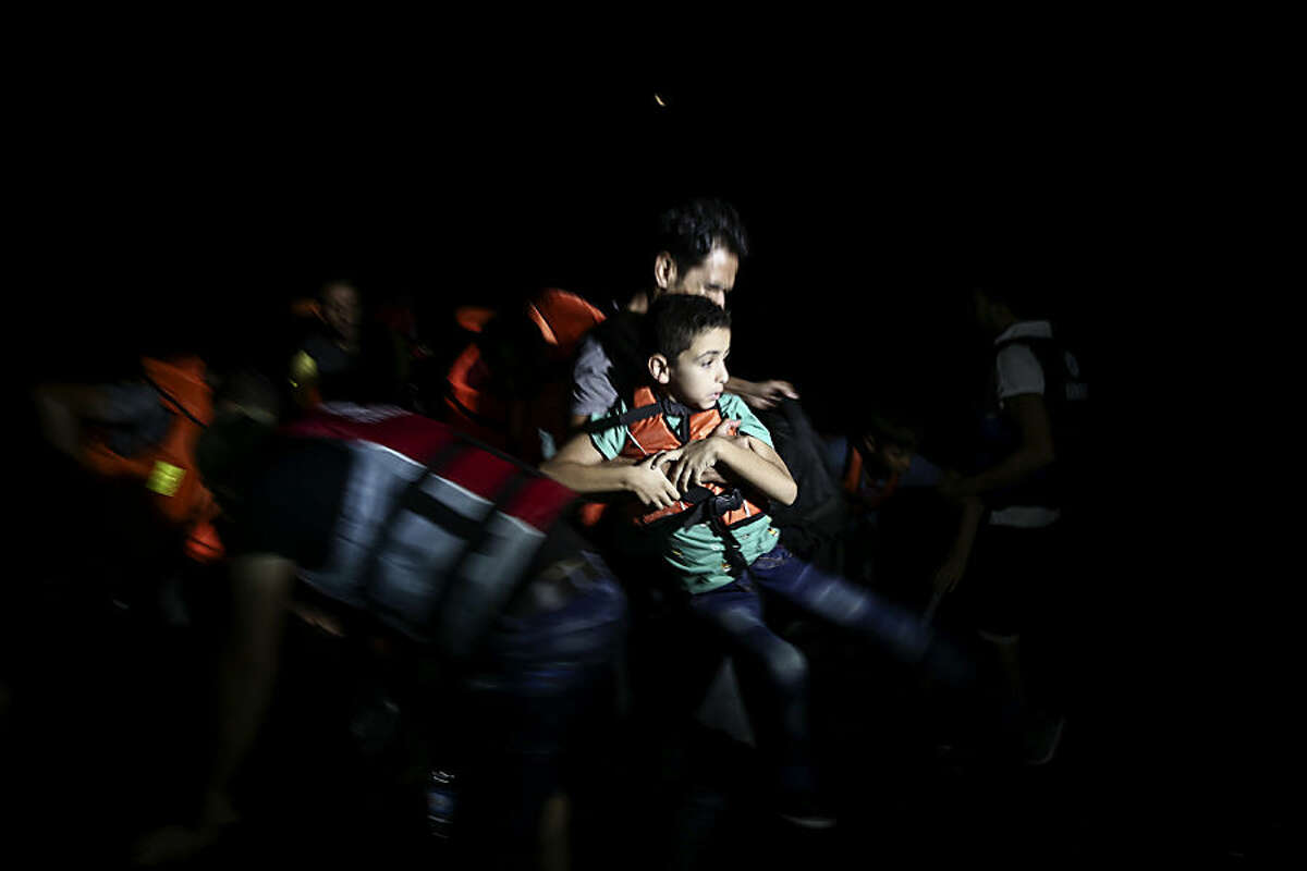 A migrant carries a child off a dinghy after crossing from Turkey to the Greek southeastern island of Kos, at the early hours, Wednesday, Aug. 12, 2015. Dozens of boat people from the Middle East are flowing into the Greek holiday island of Kos from nearby Turkey, joining thousands of refugees camped under wretched conditions. (AP Photo/Yorgos Karahalis)