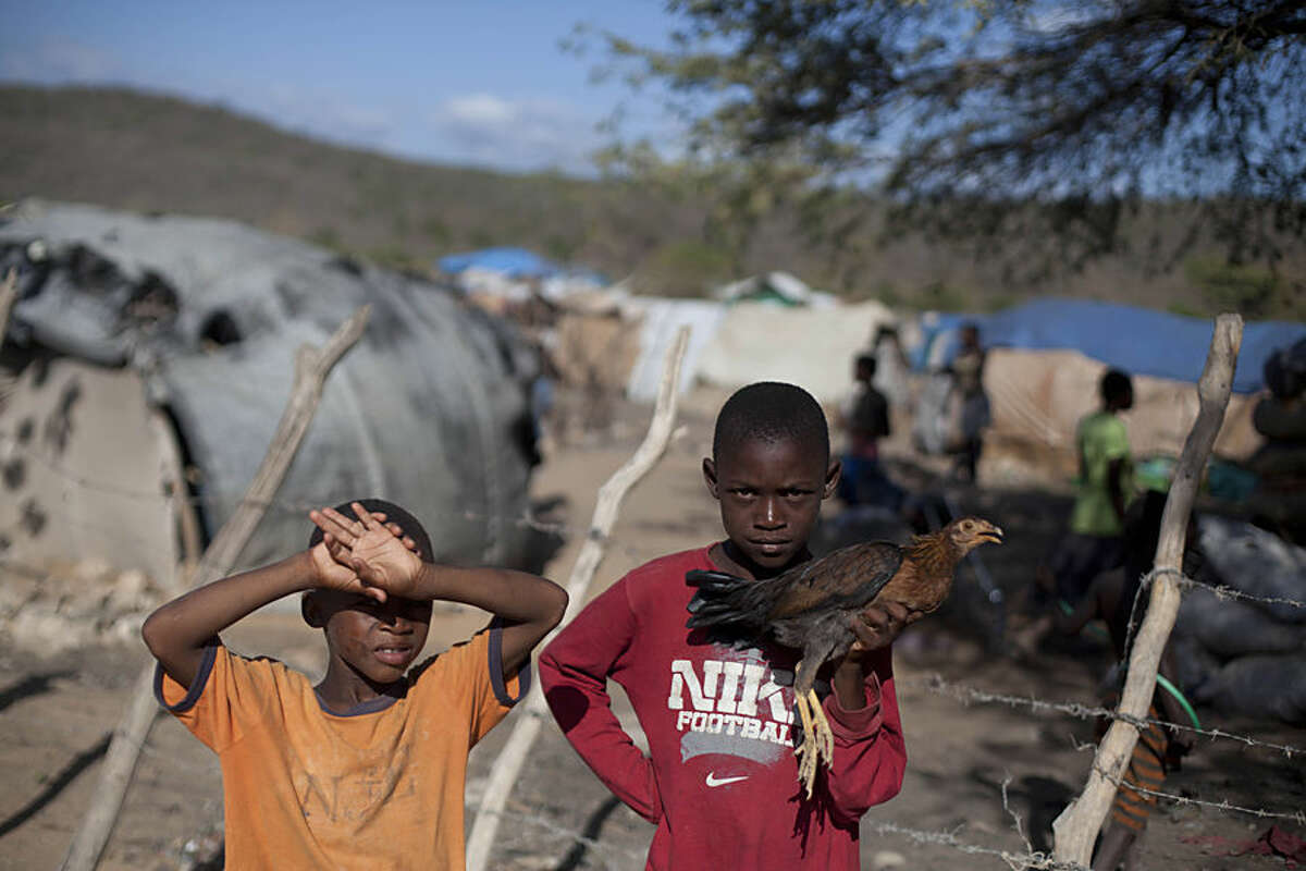 In this Aug. 3, 2015 photo, Haitian Yolner Macenat holds a chicken, alongside his little brother Yodler Macenat outside an encampment in Anse-a-Pitres, Haiti where Haitians are living after either fleeing from, or getting deported from, the Dominican Republic. Yolner brought his chicken from the D.R., and was looking for food to feed it. (AP Photo/Dieu Nalio Chery)