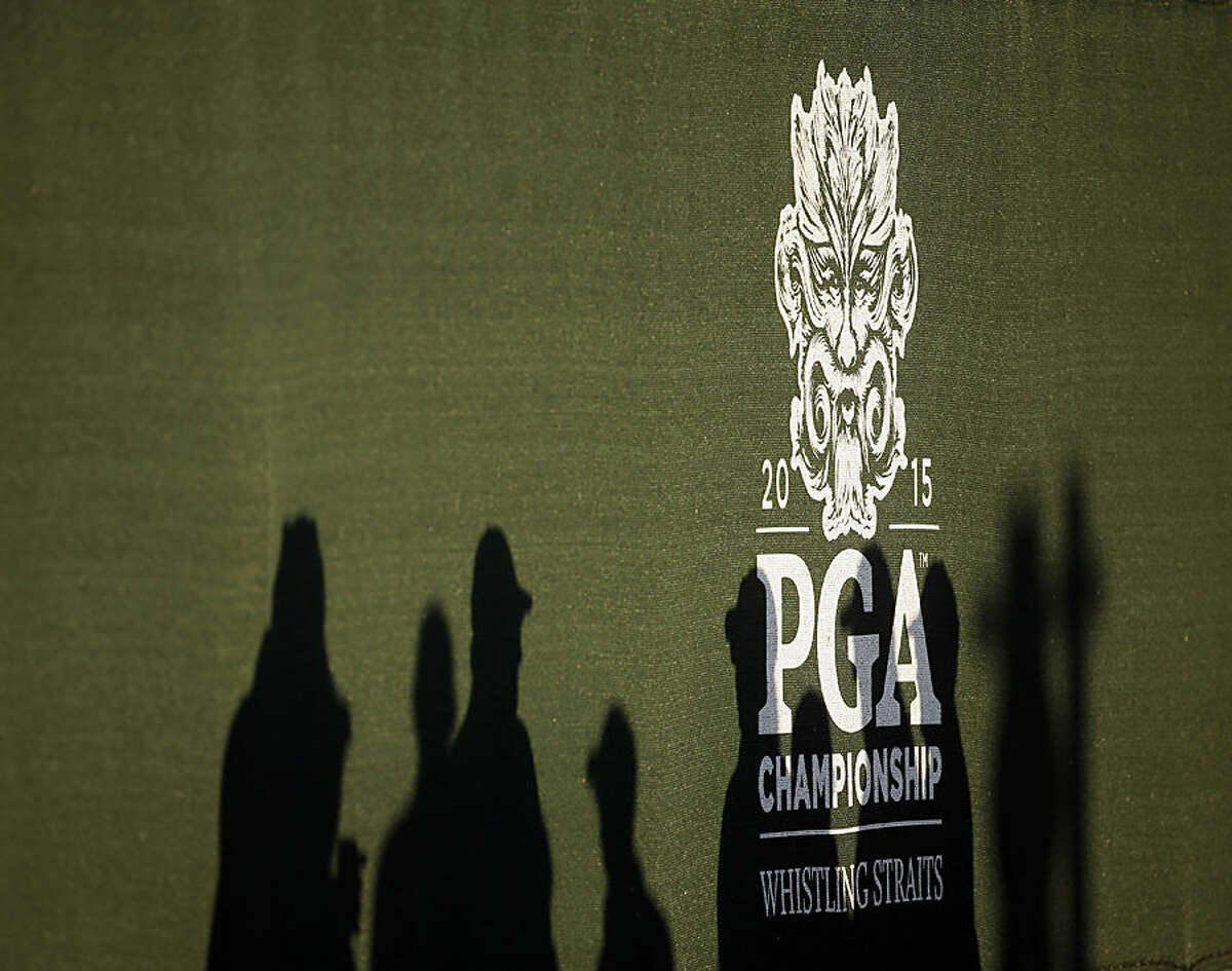 The shadows of marshals are seen at the first hole as the sun rises before a practice round for the PGA Championship golf tournament Wednesday, Aug. 12, 2015, at Whistling Straits in Haven, Wis. (AP Photo/Chris Carlson)