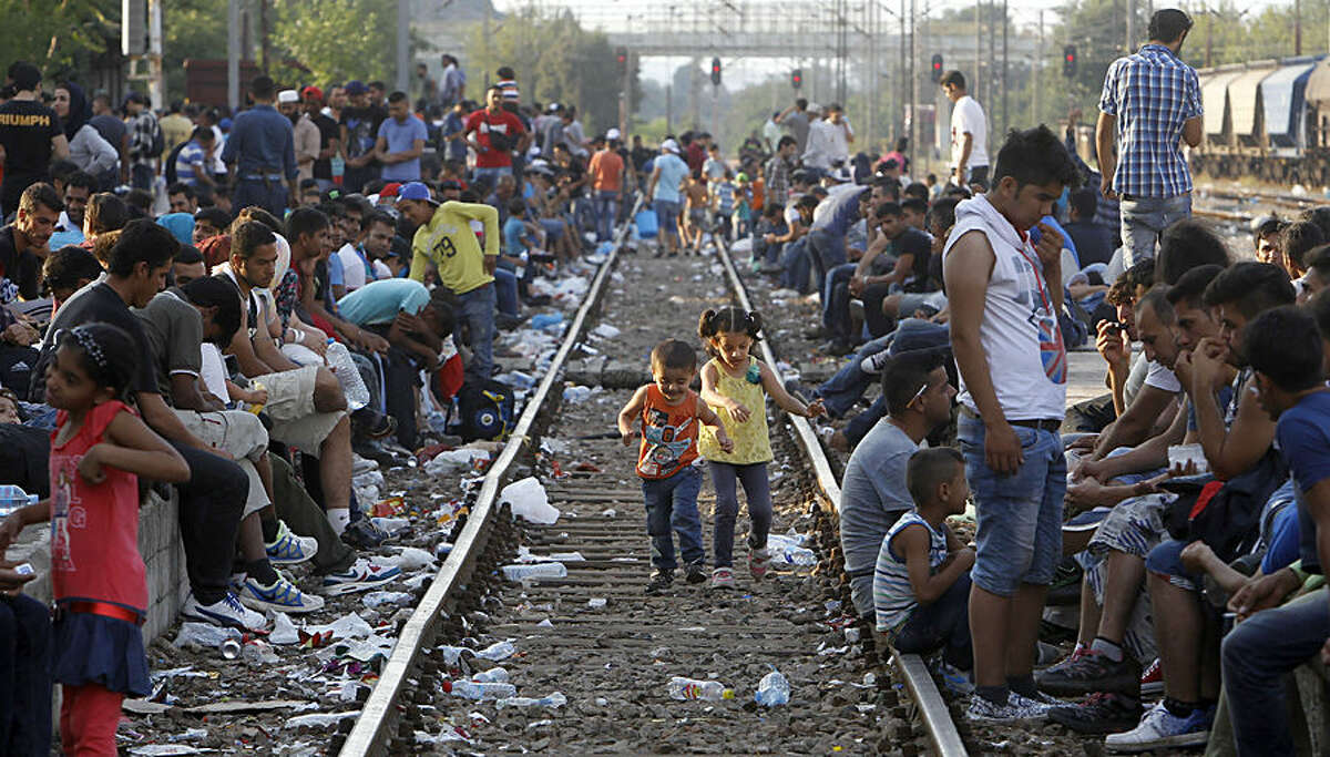 Migrants wait for a train towards Serbia, at the railway station in the southern Macedonian town of Gevgelija, Wednesday, Aug. 12, 2015. Macedonia is facing an increasing pressure of migrants flow on its southern and northern borders with Greece and Serbia as thousands of migrants from Middle East, Asia and Africa are heading north through the Balkans on their way to the more prosperous European Union countries. (AP Photo/Boris Grdanoski)