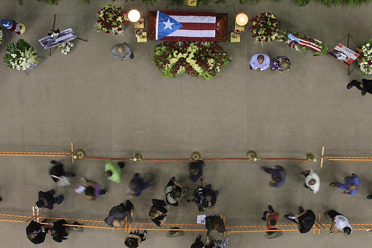 Mourners file past the casket containing the remains of Puerto Rican composer Raphy Leavitt, during his funeral at the San Juan Coliseum in Puerto Rico, Tuesday, Aug. 11, 2015. Leavitt, founder of the salsa orchestra
