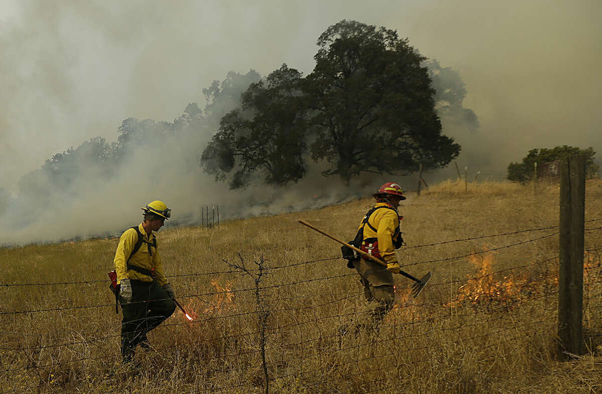 A fire crew works a back fire along Morgan Valley Road near Lower Lake, Calif., Wednesday, Aug. 12, 2015. Erratic winds fanned a wildfire burning through rugged hills in Northern California on Wednesday, pushing the flames across two counties and chasing people from their homes. (AP Photo/Jeff Chiu)