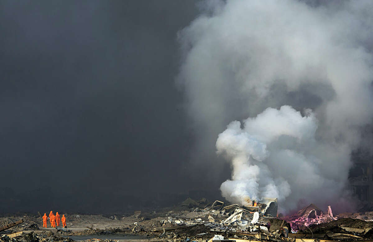 Fire fighters in protective gear watch as smoke continues to billow out after an explosion at a warehouse in northeastern China's Tianjin municipality, Thursday, Aug. 13, 2015. Huge explosions in the warehouse district sent up massive fireballs that turned the night sky into day in the Chinese port city of Tianjin, officials and witnesses said Thursday. (AP Photo/Ng Han Guan)