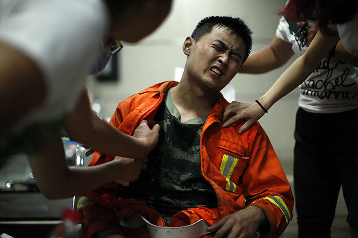 An injured firefighter grimaces as he is examined in a hospital following explosions in northeastern China's Tianjin municipality, Thursday, Aug. 13, 2015. Chinese state media reported huge explosions at the Tianjin port late Wednesday. (Chinatopix Via AP) CHINA OUT