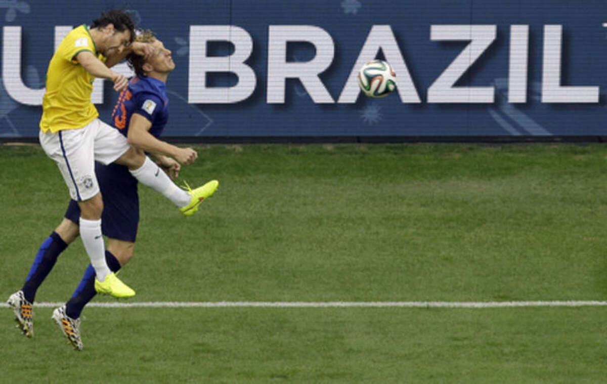 Brazil's Maxwell, left, and Netherlands' Dirk Kuyt go for a header during the World Cup third-place soccer match between Brazil and the Netherlands at the Estadio Nacional in Brasilia, Brazil, Saturday, July 12, 2014. (AP Photo/Themba Hadebe)