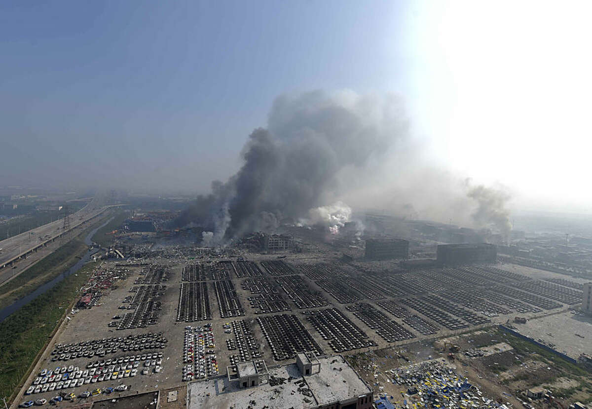 In this photo released by China's Xinhua News Agency, smoke rise from the site of explosions from a nearby building in the Binhai New Area in northeastern China's Tianjin municipality, Thursday, Aug. 13, 2015. Huge explosions in the warehouse district sent up massive fireballs that turned the night sky into day in the Chinese port city of Tianjin, officials and witnesses said Thursday. (Yue Yuewei/Xinhua via AP) NO SALES