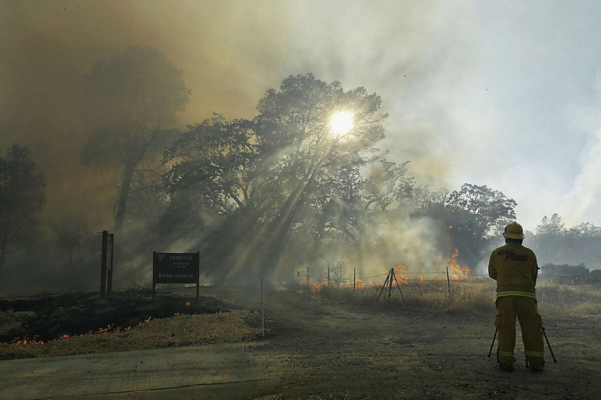 A Cal Fire photographer takes pictures of smoke from a wildfire near Lower Lake, Calif., Wednesday, Aug. 12, 2015. Erratic winds fanned a wildfire burning through rugged hills in Northern California on Wednesday, pushing the flames across counties and chasing people from their homes. (AP Photo/Jeff Chiu)