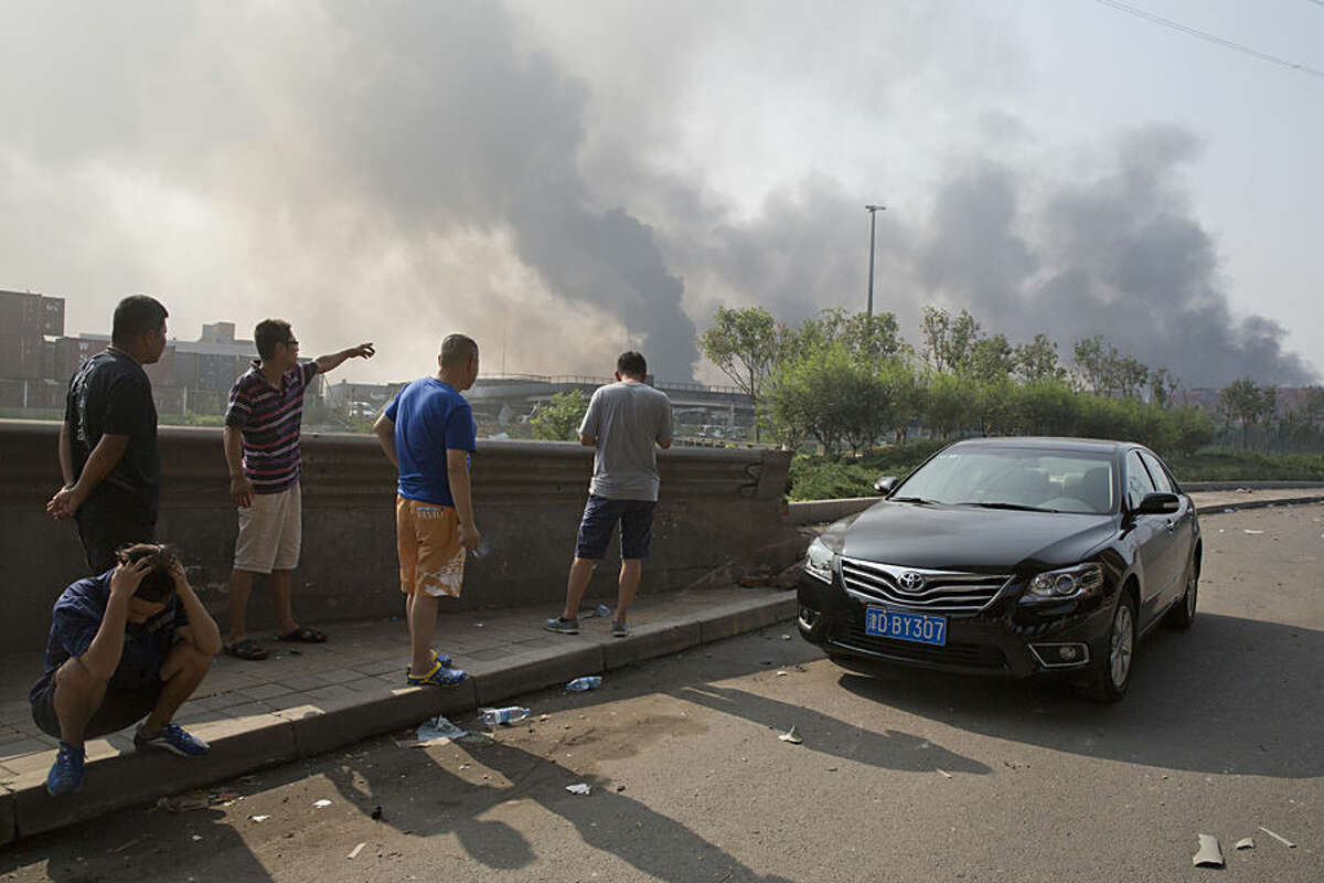 Residents gather near the site of an explosion at a port in northeastern China's Tianjin municipality, Thursday, Aug. 13, 2015. Chinese state media reported huge explosions at the Tianjin port late Wednesday. (AP Photo/Ng Han Guan)