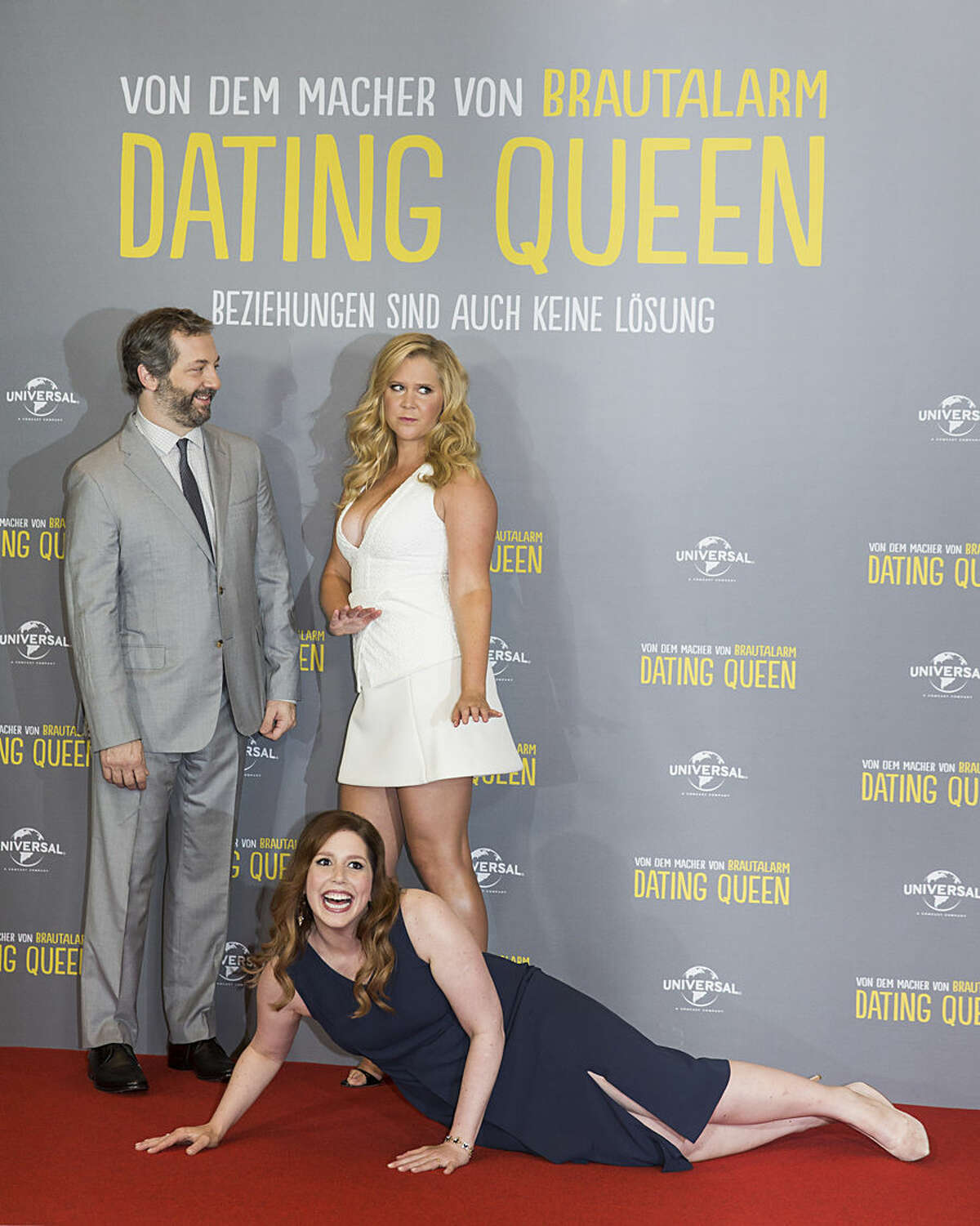 US actress Vanessa Bayer jokingly lies down in front of US actress Amy Schumer, right, and US director Judd Apatow, left, during a photo call for the movie