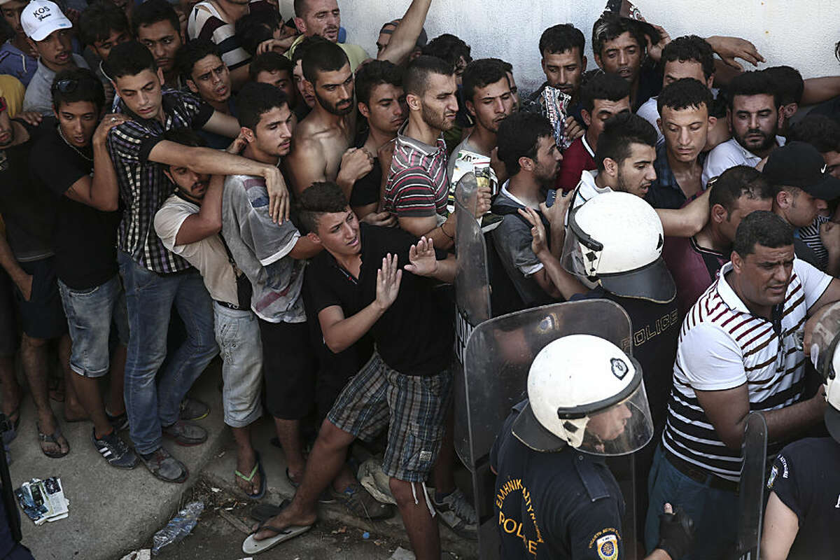 Police officers try to make space as migrants queuing for a registration procedure inside a stadium in Kos, on the Greek southeastern island of Kos, Wednesday, Aug. 12, 2015. Locked in a sunbaked football stadium without food, drinking water or sanitation, about 1,000 refugees queued for hours Wednesday to register with overwhelmed Greek authorities on the holiday island of Kos, now at the forefront of a humanitarian crisis sweeping the financially broken country. (AP Photo/Yorgos Karahalis)