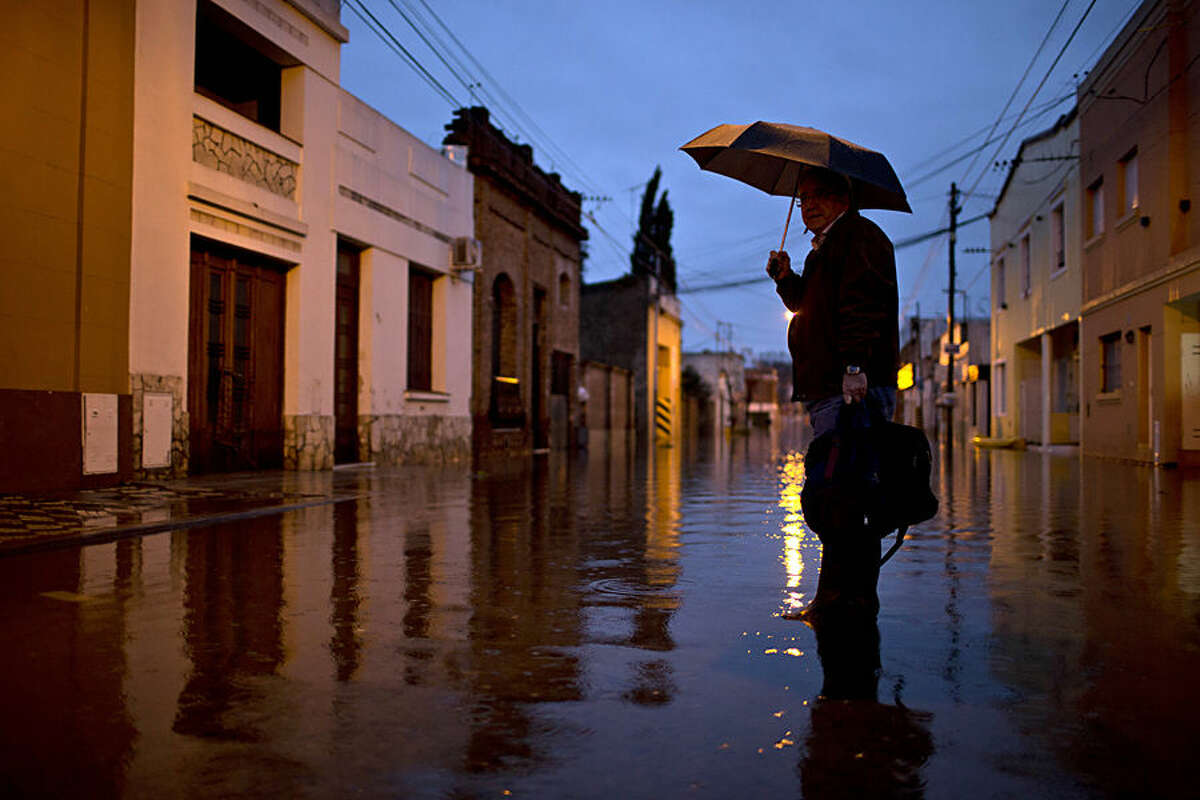 Carlos Sanchez waits for a boat to take him home, on a flooded street in Lujan, Argentina, Wednesday, Aug. 12, 2015. More than 11,000 people had been evacuated by Tuesday from parts of Argentina's largest province after heavy weekend rains caused rivers to rise precipitously, a top official said. (AP Photo/Natacha Pisarenko)