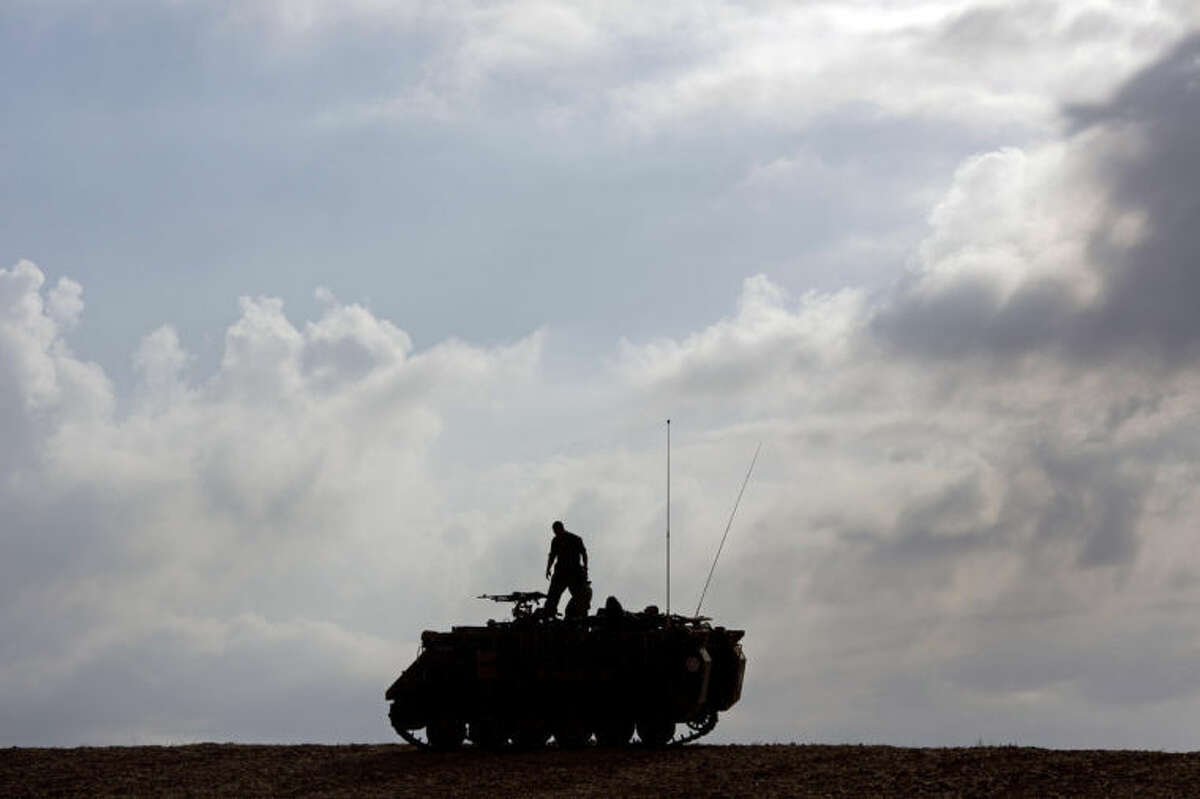 An Israeli soldiers on top a military vehicle near the Israel Gaza Border, early Tuesday, July 15, 2014. The Israeli Cabinet has accepted an Egyptian proposal for a cease-fire to end a week of conflict with Hamas militants in the Gaza Strip that has killed 185 Palestinians and exposed millions of Israelis to Hamas rocket fire. No Israelis have been killed as a result of Hamas rocket launches. A senior Hamas official says the Palestinian militant group rejects an Egyptian proposal for a cease-fire with Israel. (AP Photo/Ariel Schalit)