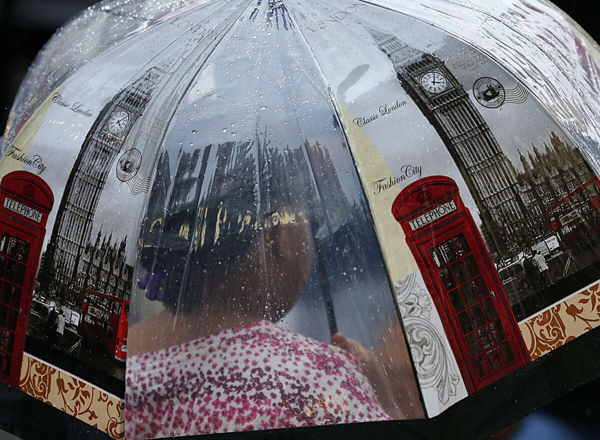 A woman holds an umbrella as she walk through torrential rain in London, Thursday, Aug. 13, 2015. Heavy rain is expected to fall for several hours in the capital. (AP Photo/Frank Augstein)