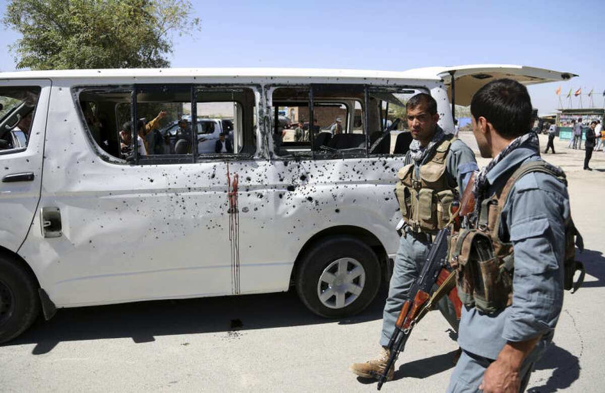 Afghan security personnel walk by a damaged vehicle after it was hit by a remote-controlled bomb on the outskirts of Kabul, Afghanistan, Tuesday, July 15, 2014. Gul Agha Hashimi, the chief of criminal investigations with the Kabul police, says the explosion struck a minivan carrying seven staffers of the palace's media office on Tuesday morning. The blast killed two passengers and also wounded five people, including the driver. (AP Photo/Rahmat Gul)